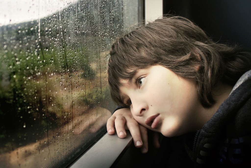Boy on train, rain on window