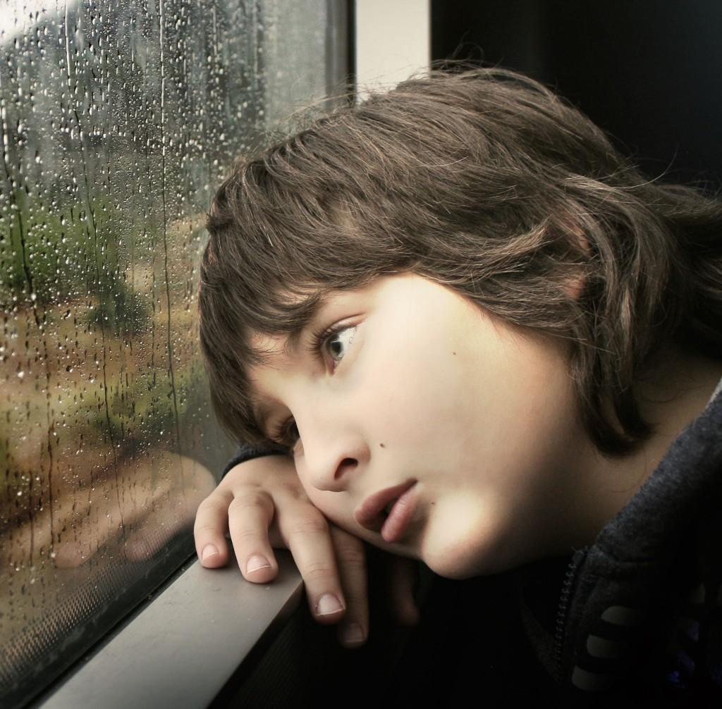 Sad boy on train, rain on window square